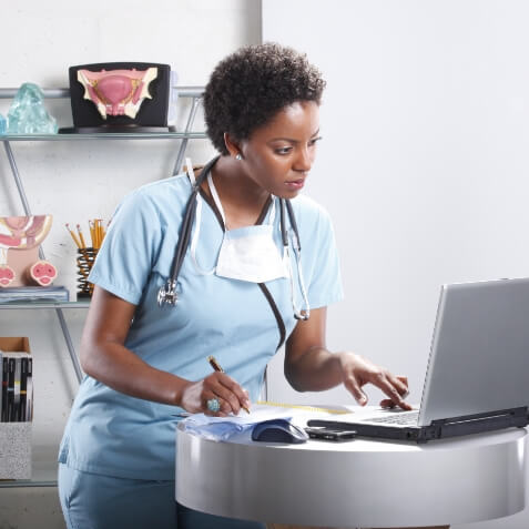 A nurse working at a laptop.